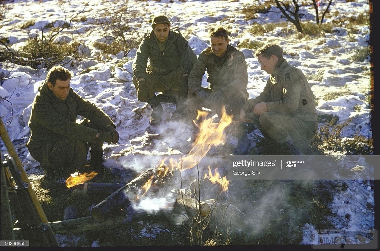 109239 - Четверо американских солдат греются у костра на опушке Арденнского леса. Декабрь 1944 года.