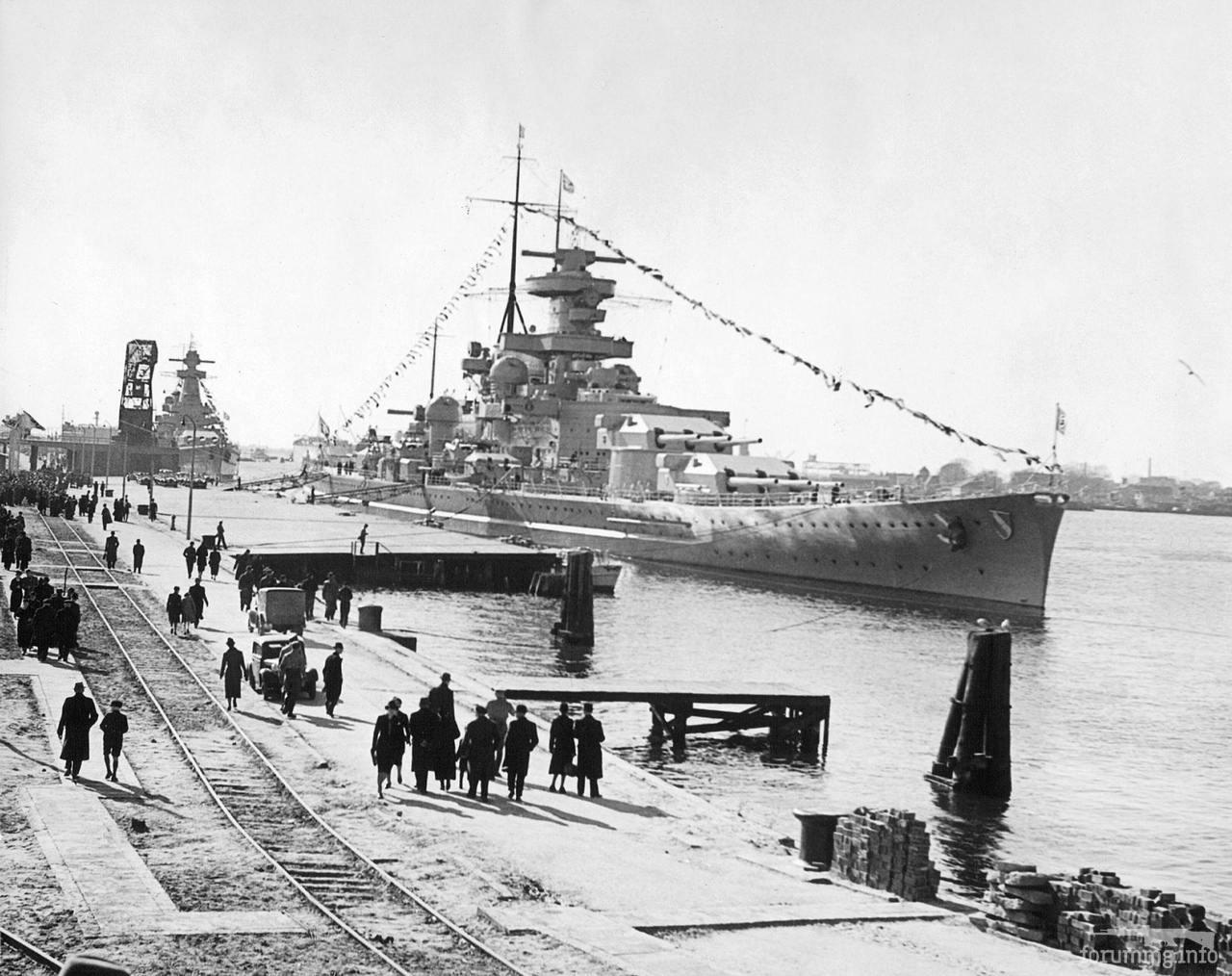 """118219 - Линкор Scharnhorst в Вильгельмсхафене, 2 апреля 1939 г. Корабль украшен флагами по случаю спуска на воду линкора Tirpitz и визита фюрера. За ним """"карманный линкор"""" Admiral Graf Spee."""