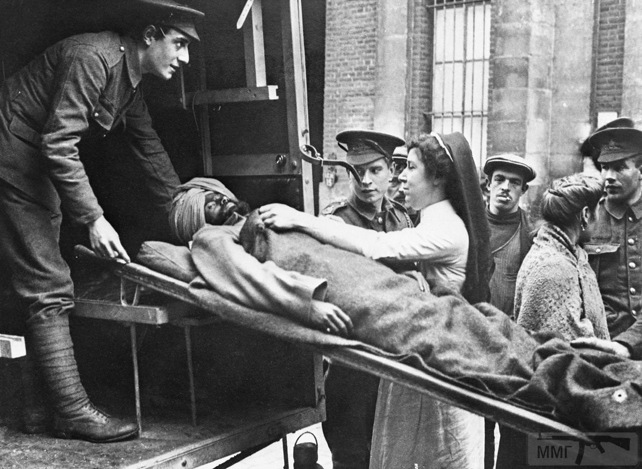 19244 - Британская медсестра поправляет одеяло раненому индийскому солдату, носилки с которым грузят в санитарный грузовик, Западный фронт, 25 октября 1914 г.