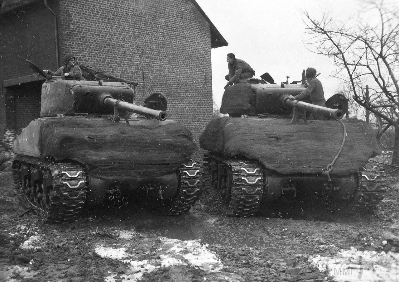 20229 - Танки М4А3(76) «Sherman» 747-го батальона США в немецком городе Шлайден. Германия, 31 января 1945 года. На машины была установлена дополнительная защита, в виде запасных траков и мешков с песком, укрытых камуфляжной сетью. Батальон действовал с 29-й пехотной дивизией США.
