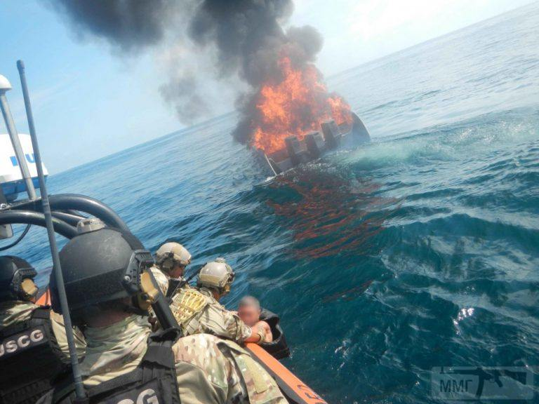 25692 - Моторная лодка со сторожевого катера РС 8 Zephyr ВМС США подходит к горящему подожженому малозаметному скоростному катеру колумбийских наркоторговцев и поднимает контрабандистов из воды.