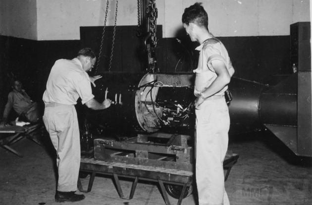 """3153 - Командир А.Ф. Бирч (слева) нумерует бомбу под кодовым названием «Малыш» перед погрузкой ее на трейлер в здании Ассамблеи №1 перед конечной погрузкой бомбы на борт бомбардировщика B-29 Superfortress """"Enola Gay"""" на базе 509-ой сводной группы на острове Тиниан у Марианских островов в 1945 году. Физик доктор Рамсей (справа) получит Нобелевскую премию в области физики в 1989 году. (U.S. National Archives)"""