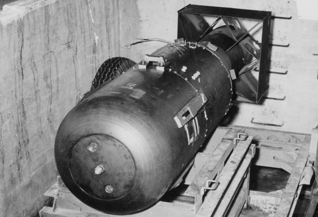"""3154 - «Малыш» покоится на трейлере в яме над шлюзом бомбардировщика B-29 Superfortress """"Enola Gay"""" на базе 509-ой сводной группы на Марианских островах в 1945 году. «Малыш» составлял 3 м в длину и весил 4 000 кг, но содержал всего 64 кг урана, который использовался для провоцирования цепочки атомных реакций и последующего взрыва. (U.S. National Archives)"""