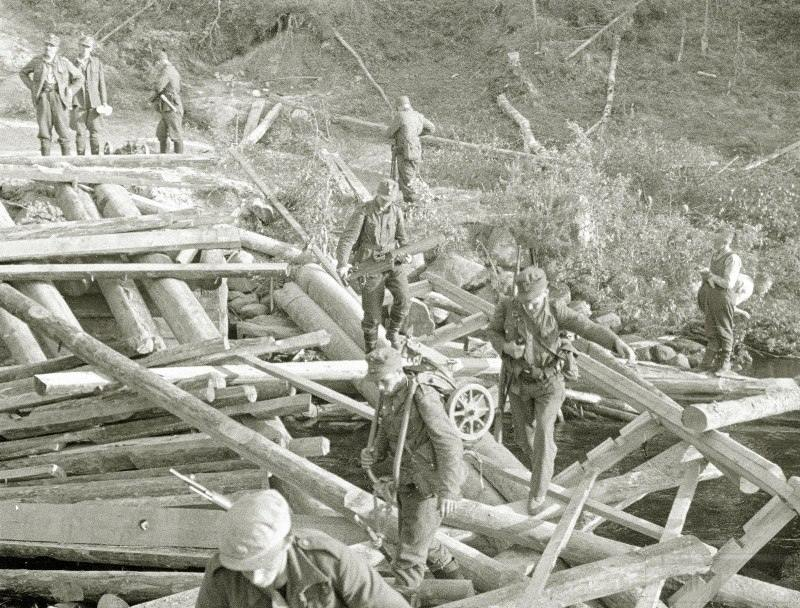 4273 - Финские пехотинцы перебераються через речку по обломкам, взорванного красноармейцами при отходе, моста