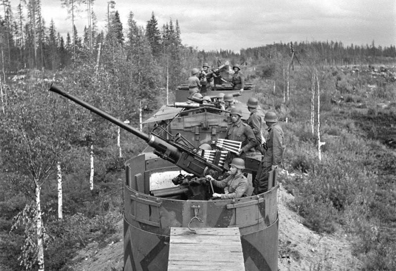 5354 - Расчеты зенитного орудия и пулеметов финского бронепоезда демонстрируют готовность открыть огонь. На преднем плане — расчет у 40-мм автоматического зенитного орудия Бофорс L60. За ним видны платформы с расчетами у пулеметов «Максим», приспособленными для стрельбы, как по наземным, так и по воздушным целям.