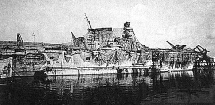 8610 - Work on Aquila was stopped by 1943 and she rusted in Genoa harbour, with a half-hearted attempt to conceal her identity with camouflage nets