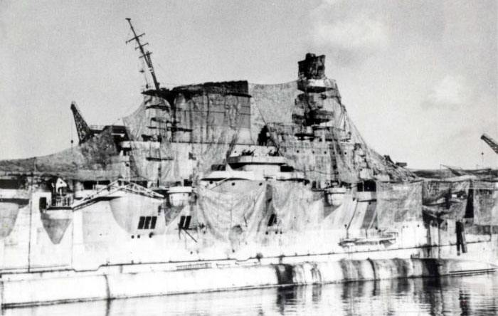 8613 - A close-up of Aquila's island superstructure draped with camouflage netting at Genoa in August 1943